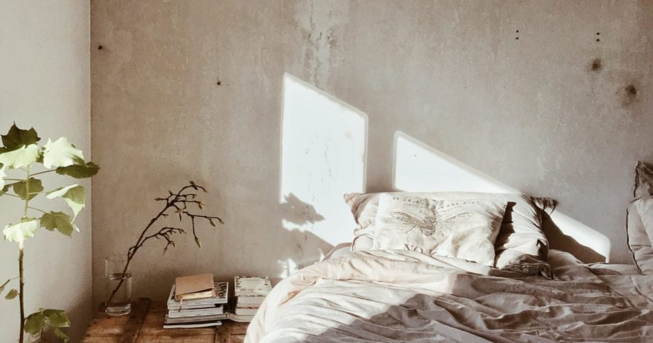 Photograph of a bedroom with sunlight coming in